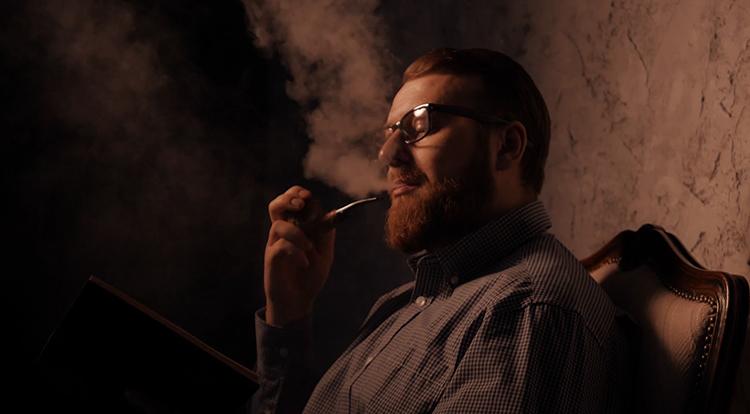 Мужчина курит трубку