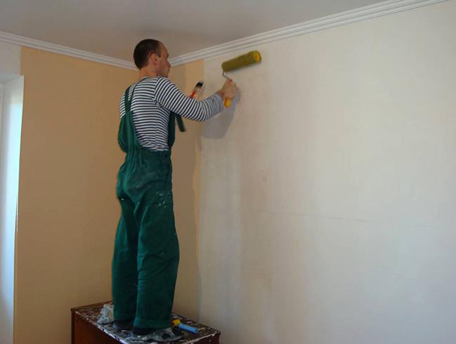 Специалист красит стену